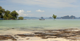 Belle plage avec des vues de mer et un bateau de pêche thaïlandais traditionnel Belle plage avec les arbres tropicaux avec une va Images stock