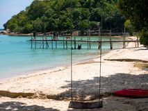 Belle plage avec le ciel bleu et un bateau sur le dock Image libre de droits