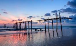 Belle plage de coucher du soleil avec le pilier en bois abandonné Images stock