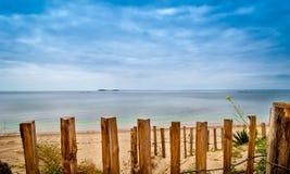 Belle plage en Bretagne avec les enjeux en bois photographie stock libre de droits