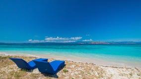 Belle plage Lits pliants avec le parapluie sur la plage sablonneuse près de la mer Photos stock