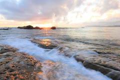 Belle plage rocheuse illuminée par les rayons d'or de la lumière du soleil de matin à la côte de Yehliu, Taïpeh, Taïwan Image libre de droits