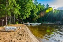 Belle plage sablonneuse abandonnée d'un lac de forêt avec des chaises longues et des bateaux amarrés au soleil Image stock