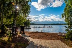 Belle plage sablonneuse abandonnée d'un lac de forêt avec des lits du soleil et un pilier pour pêcher au soleil Images libres de droits