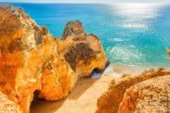 Belle plage sablonneuse parmi des roches et des falaises région près de Lagos, Algarve, Portugal Photos stock