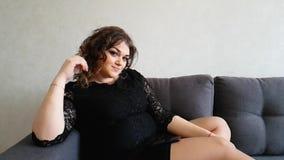 Belle pleine fille s'asseyant sur le divan, triste, rêver romantique de vacances banque de vidéos