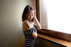 Belle pose asiatique sensuelle de femme réfléchie à la fenêtre Images stock