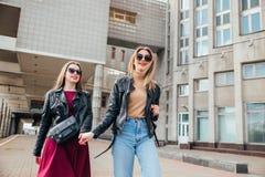 Belle pose de femmes de mode Portrait urbain de mode de vie à la mode sur le fond de ville amie élégante dans des lunettes de sol Image stock