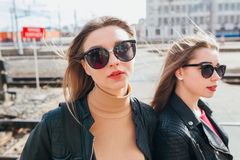 Belle pose de femmes de mode Portrait urbain de mode de vie à la mode sur le fond de ville amie élégante dans des lunettes de sol Photos stock