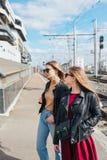 Belle pose de femmes de mode Portrait urbain de mode de vie à la mode sur le fond de ville amie élégante dans des lunettes de sol Image libre de droits