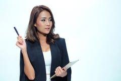 Belle position asiatique de femme de portrait, comprimé de prise et stylo Photo libre de droits