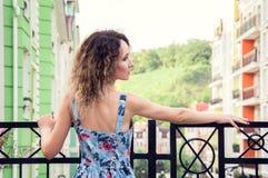 Belle position mince de fille sur le balcon Elle a tourné elle de nouveau à la caméra et des regards vers la droite Vieille rue m photographie stock libre de droits