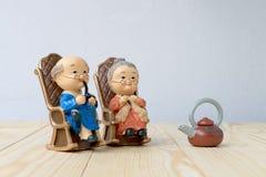 Belle poupée de grand-parent situant la chaise classique de vieux sofa ensemble sur la table en bois avec le fond Images stock