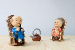 Belle poupée de grand-parent situant la chaise classique de vieux sofa ensemble sur la table en bois avec le fond Photo stock