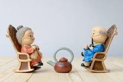 Belle poupée de grand-parent situant la chaise classique de vieux sofa ensemble sur la table en bois avec le fond Photographie stock libre de droits