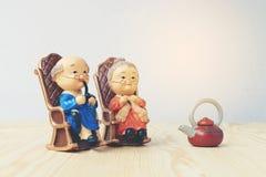 Belle poupée de grand-parent situant la chaise classique de vieux sofa ensemble sur la table en bois avec le fond Photos stock