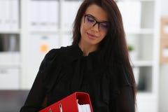 Belle prise de sourire de femme de brune dans la reliure de rouge de bras Photos libres de droits