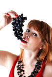 Belle prove della ragazza per mangiare l'uva Fotografia Stock
