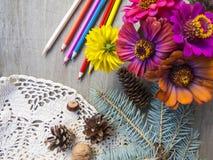 Belle rétro photo avec des fleurs, des cônes de pin et des crayons sur un fond en bois Photo libre de droits