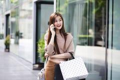 Belle ragazze asiatiche con i sacchetti della spesa facendo uso dello smartphone Fotografia Stock
