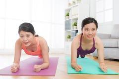 Belle ragazze che fanno il corpo di allenamento di posizione della plancia Fotografia Stock