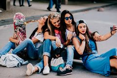 4 belle ragazze che si siedono sulla strada Immagine Stock Libera da Diritti