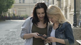 Belle ragazze che vanno in giro avendo una conversazione e per mezzo degli smartphones mentre camminando video d archivio
