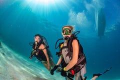 Belle ragazze che vi esaminano mentre nuotando underwater immagine stock