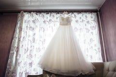 Belle robe de mariage blanche sur le cintre sur le fond d'une fenêtre Image libre de droits