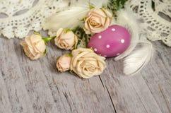 Belle rose beige con l'uovo di Pasqua, le piume ed il tovagliolo tricottato su una tavola di legno strutturata Grande retro proge Fotografie Stock Libere da Diritti