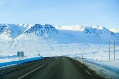 Belle route avec la montagne couronnée de neige pendant l'hiver en Islande Photographie stock libre de droits