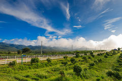 Belle route de campagne dans le domaine vert sous le ciel bleu Photo stock