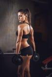 Belle séance d'entraînement musculaire sportive de femme dans le gymnase Photo libre de droits