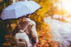 Belle saison d'or d'automne Aquarelle comme la fille blonde brouillée avec le sac à dos et supports de parapluie lumineux sous pl Photo stock