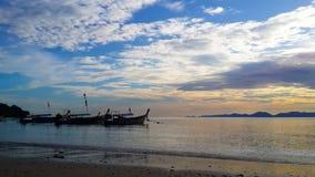 Belle scène de coucher du soleil à la plage lumière du soleil de observation et bateau de ciel bleu Photographie stock libre de droits