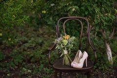 Belle scarpe di nozze con i tacchi alti e un mazzo dei fiori variopinti su una sedia d'annata sulla natura alla luce di tramonto, Immagine Stock