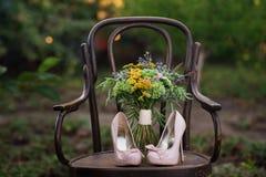 Belle scarpe di nozze con i tacchi alti e un mazzo dei fiori variopinti su una sedia d'annata sulla natura alla luce di tramonto, Fotografia Stock