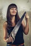 Belle scie de fixation de jeune fille au-dessus de grunge Photographie stock libre de droits