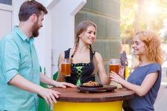 Belle serveuse dans le costume allemand traditionnel tenant le verre de bière dans la barre Photos libres de droits