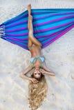 Belle, sexy femme dans le bikini posant sur un hamac sur la plage des Caraïbes Photos stock