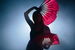 Belle silhouette d'une fille dansant d'une manière élégante en fumée et brouillard photos libres de droits