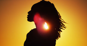 Belle silhouette de femme africaine se tenant au coucher du soleil Photos stock