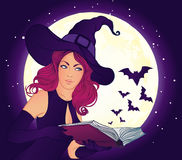 Belle sorcière avec le livre magique Photographie stock