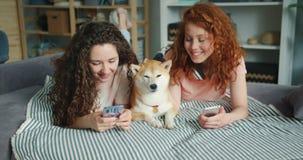 Belle sorelle facendo uso della menzogne canina sveglia di coccole e dello smartphone sullo strato a casa video d archivio