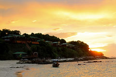 Belle spiaggia e barca di tramonto vicino alla località di soggiorno di montagna Fotografia Stock Libera da Diritti