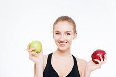 Belle sportive heureuse tenant les pommes vertes et rouges Photographie stock