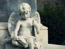 Belle statue d'enfant d'ange tenant une lyre sous son bras et un livre sur ses genoux De la ville baroque de Noto, la Sicile Photos libres de droits