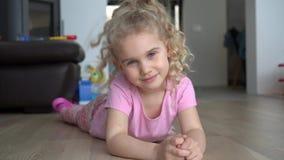 Belle tête de secousse d'enfant de fille se trouvant sur le plancher et la pose Tir de mouvement de cardan banque de vidéos