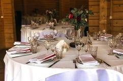 Belle table décorée élégante avec les ustensiles, vases de fleur Photographie stock