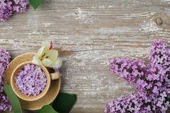 Belle tasse de fleurs lilas sur un vieux conseil texturisé Image libre de droits